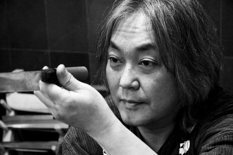 Chiharu Sugai examining a knife at Korin Japanese Trading, Corp
